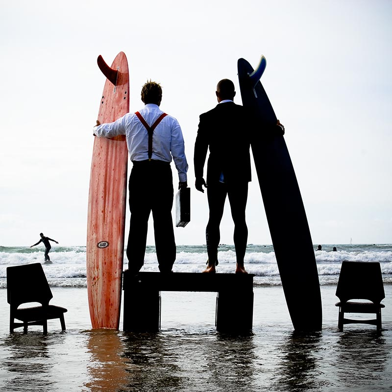 Men in suits with surf boards at Polzeath beach